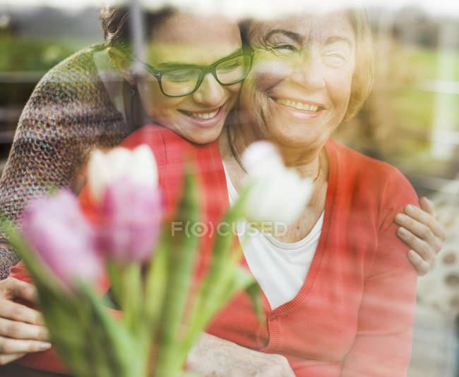 Smiling young woman hugging senior woman behind windowpane — Stock Photo