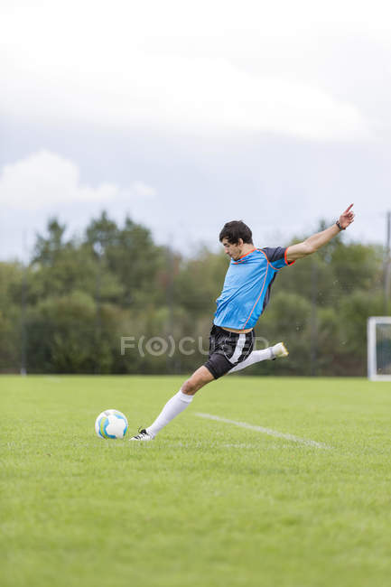 Fußball-Spieler treten Ball am Sportplatz — Stockfoto