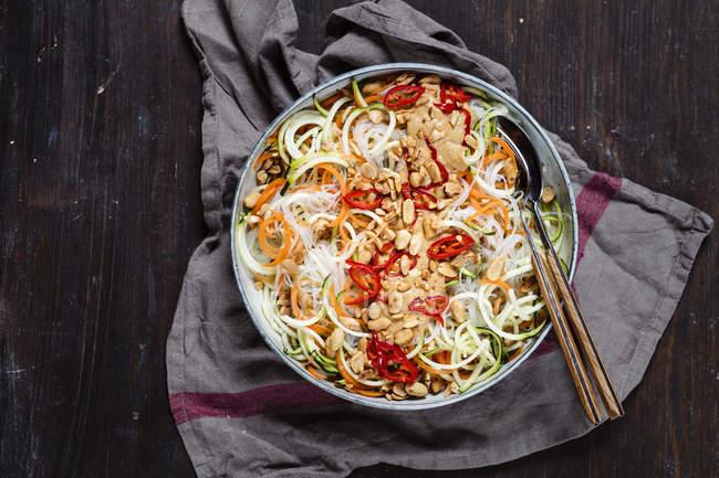 Insalata del vegan con spiralate zucchine, carote, pasta di vetro e condimento piccante di arachidi — Foto stock