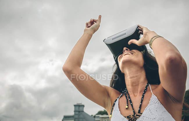 Улыбающаяся женщина с помощью очков виртуальной реальности на открытом воздухе — стоковое фото
