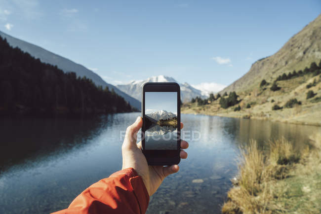 France, Pyrenees, Carlit, male hand taking a picture at mountain lake — Stock Photo