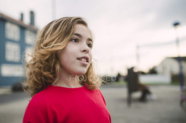 Portrait of little blonde girl wearing red pullover — Stock Photo