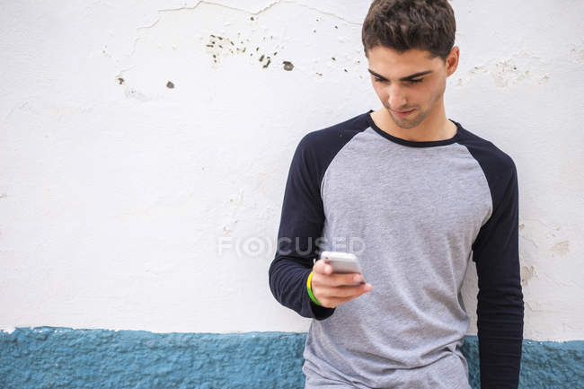 Young man at a wall looking on cell phone — Stock Photo