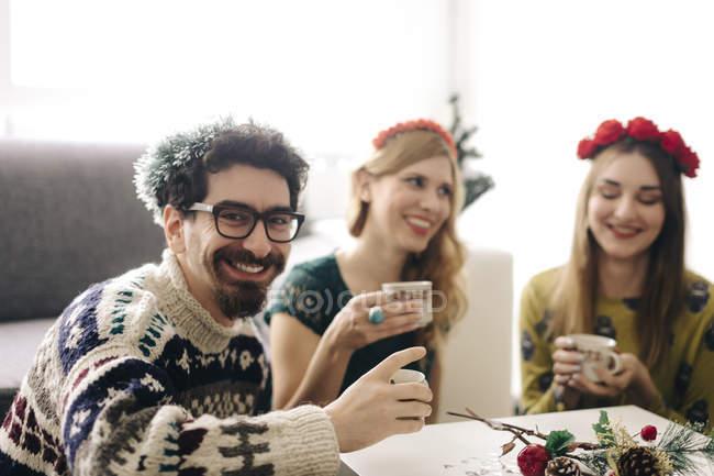 Ritratto di uomo sorridente che si rilassa con gli amici nel periodo natalizio — Foto stock