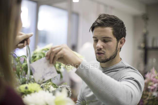 Man putting greeting card in flower arrangement — Stock Photo