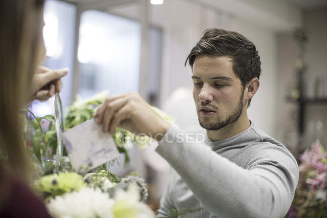 Man putting greeting card in flower arrangement — Stock Photo