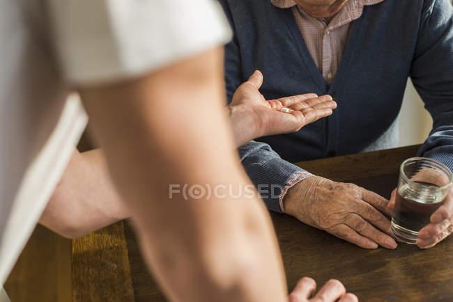 Hand eines jungen Mannes reicht Senioren sein Tablet — Stockfoto