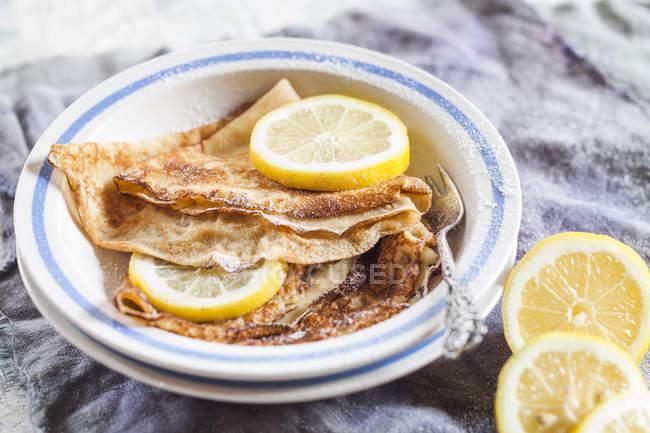 Блинчики с дольками лимона, посыпают сахарной пудрой — стоковое фото