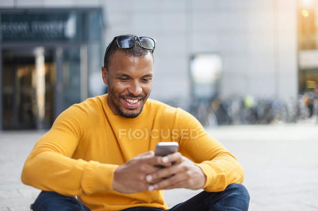 Smiling man wearing yellow pullover using cell phone — Stock Photo