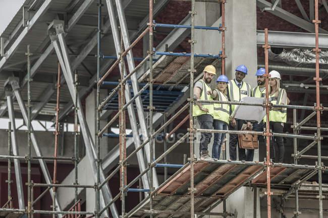 Operai e architetti edili con progetto di costruzione su ponteggi — Foto stock
