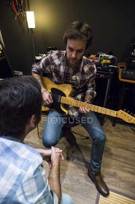 Гитарист разговаривает с человеком в студии звукозаписи — стоковое фото