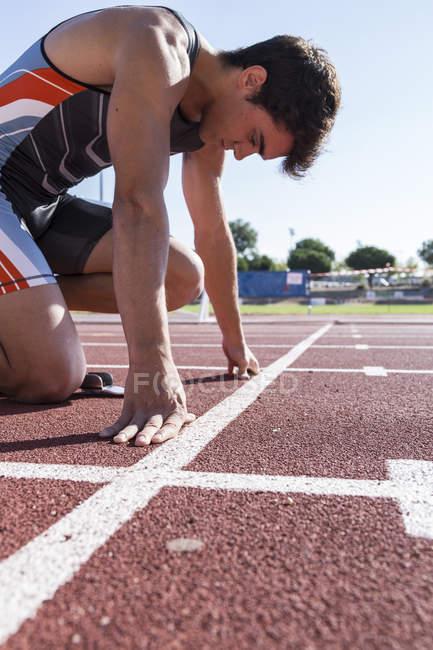 Läufer auf Tartanbahn in Startposition — Stockfoto