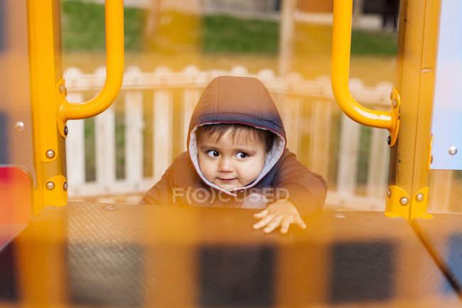 Portrait d'un petit garçon grimpant sur un équipement de terrain de jeu — Photo de stock