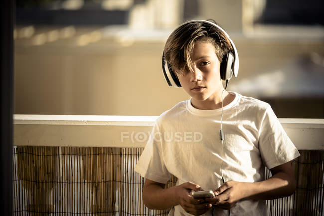 Portrait of boy listening music with headphones and smartphone on balcony — Stock Photo