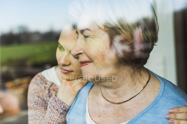 Young woman and senior woman hugging behind windowpane — Stock Photo