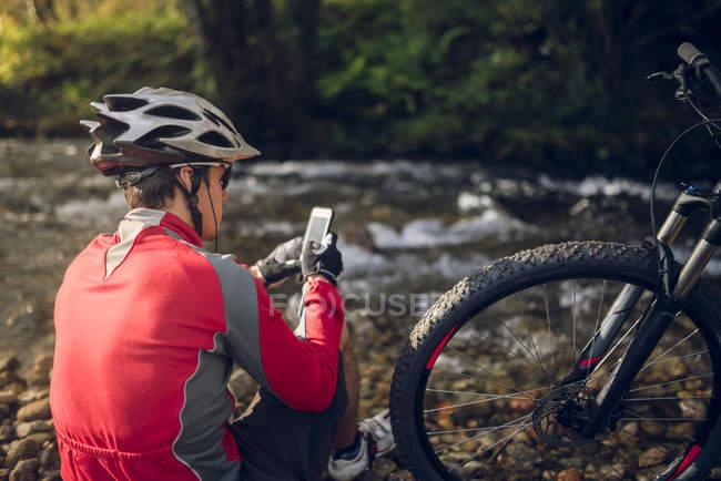 Mountain bike con smartphone al fiume — Foto stock