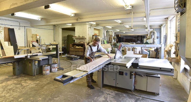 Carpenter working in workshop with wooden boards — Stock Photo