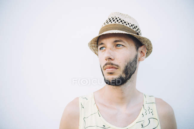Portrait of bearded man wearing straw hat and tank top in front of light background — Stock Photo
