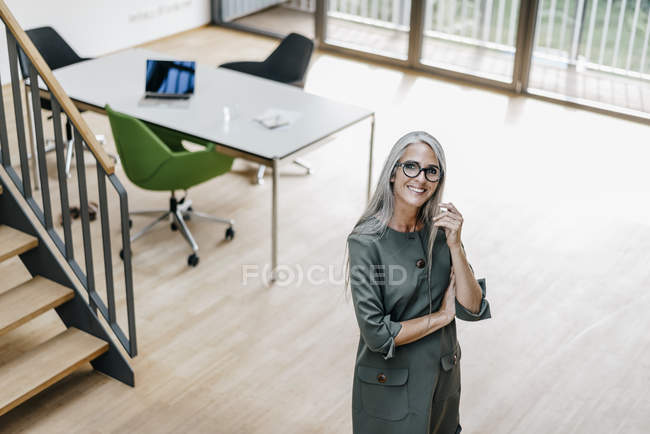 Portrait of smiling woman with long grey hair standing in office — Stock Photo
