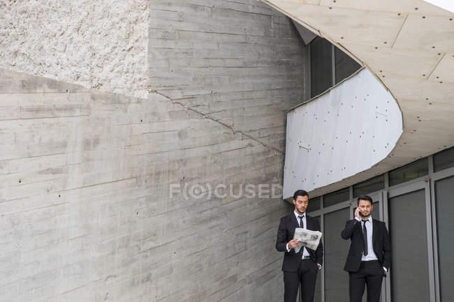 Двоє бізнесменів, носити чорні костюми перед сучасної архітектури — стокове фото