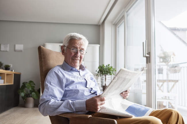 Portrait of senior man sitting on armchair at home reading newspaper — Stock Photo