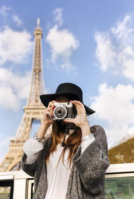 Francia, Parigi, donna che scatta una foto davanti alla Torre Eiffel — Foto stock