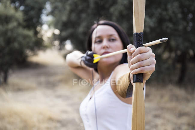 Young sporty archeress aiming with a bow — Stock Photo