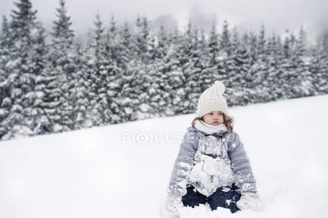Девочка сидит в зимний пейзаж на снегу — стоковое фото