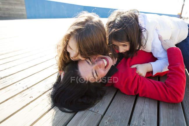 Мать и две ее дочери играют на палубе — стоковое фото