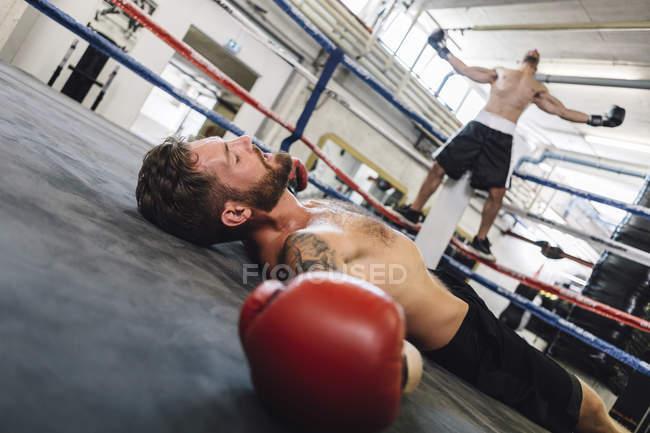 Geschlagener kaukasischer Boxer liegt im Boxring — Stockfoto