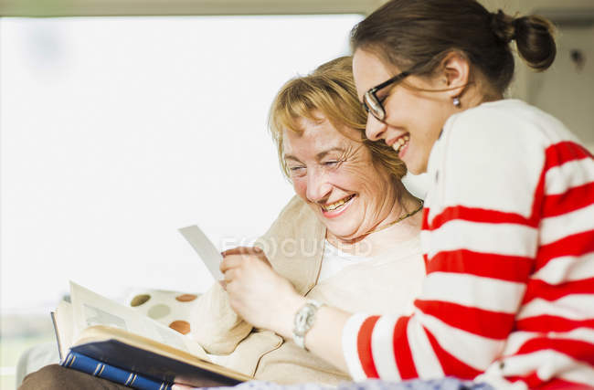Happy senior woman and young woman sitting on couch and watching photo album — Stock Photo
