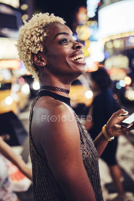African american woman with cellphone on Times Square at nighttime, NY, EUA — Fotografia de Stock