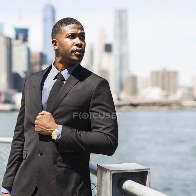 США, Бруклин, портрет бизнесмена перед горизонтом Манхэттена — стоковое фото