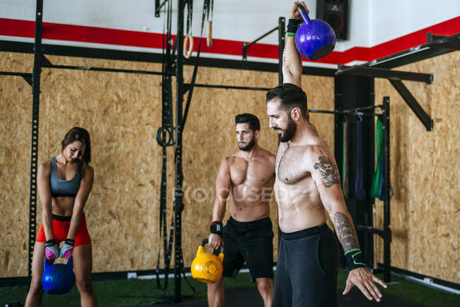 Group of athletes lifting kettlebells in gym — Stock Photo