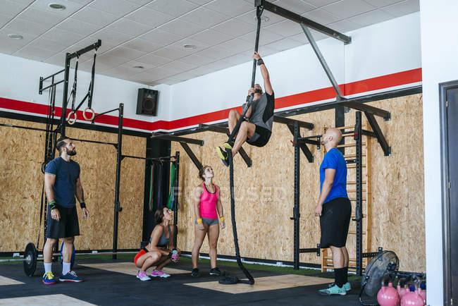 Groupe d'athlètes regarder homme escaladant une corde dans une salle de sport — Photo de stock