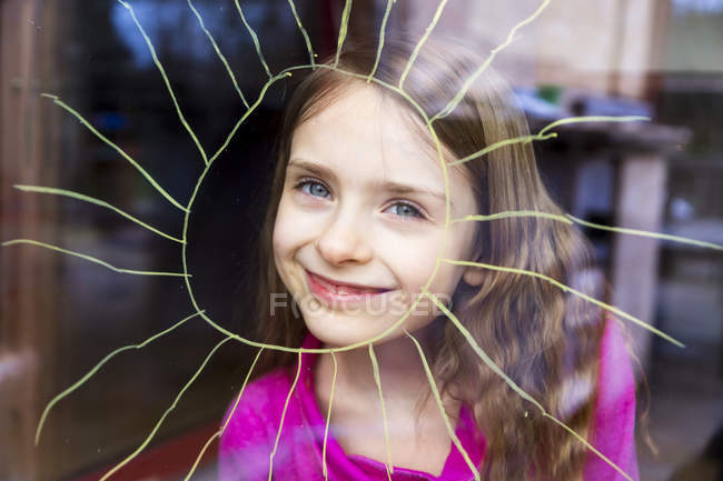 Portrait of smiling girl looking through windowpane with painted sun — Stock Photo