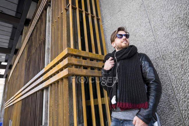 Человек в солнечных очках и наушниках стоит перед фасадом дома — стоковое фото
