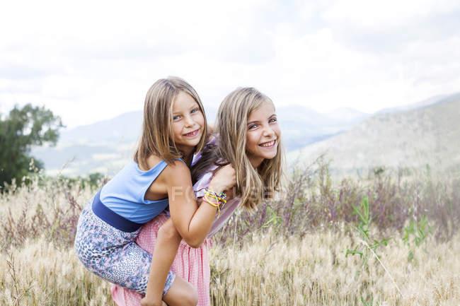 Испания, Жирона, портрет двух счастливых сестер, играющих на лугу — стоковое фото