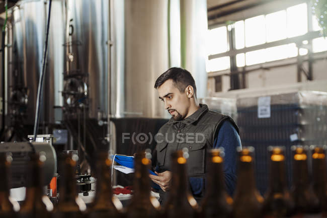 Young man working in craft brewery — Stock Photo