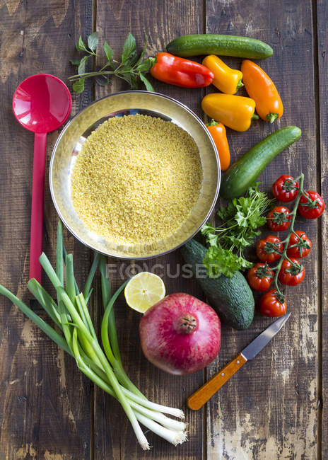 Ingredients for vegan bulgur salad including tomatoes, cucumbers, paprika, avocado and pomegranate seeds — Stock Photo