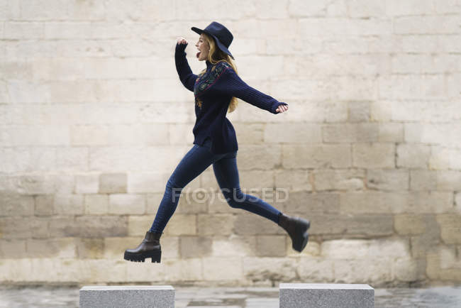 Young woman jumping from bollard to bollard — Stock Photo