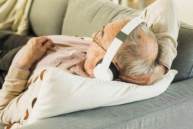 Старший лежал на диване, слушая музыку в наушниках — стоковое фото