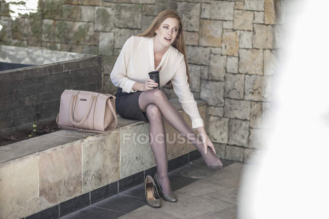 Young businesswoman taking a break, sitting on bench rubbing feet — Stock Photo