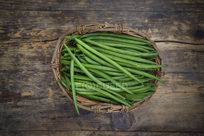 Cestino di vimini di fagiolini su legno scuro — Foto stock