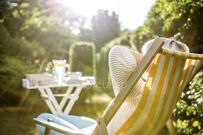 Mature woman relaxing in deckchair in garden — Stock Photo