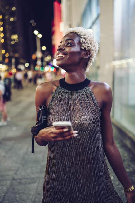 Счастливая африканская женщина с мобильным телефоном на Таймс-сквер в ночное время, штат Нью-Йорк, США — стоковое фото