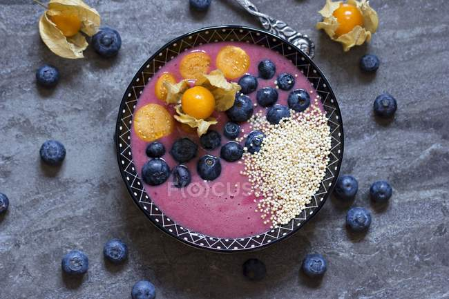 Bowl of blueberry smoothie with popped amarant, blueberries and physalis — Stock Photo