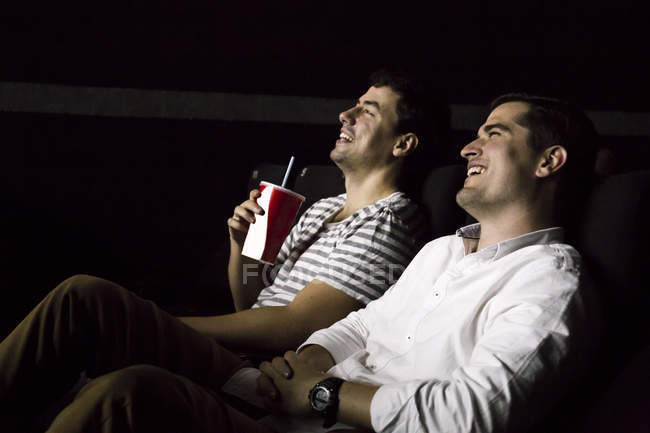 Two men watching a movie in a cinema — Stock Photo