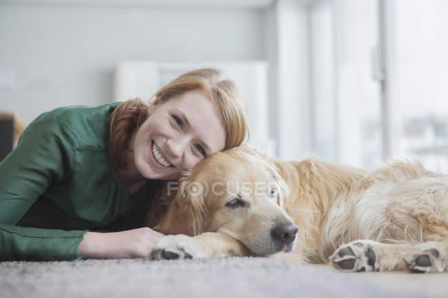 Mulher deitada com cachorro no tapete — Fotografia de Stock