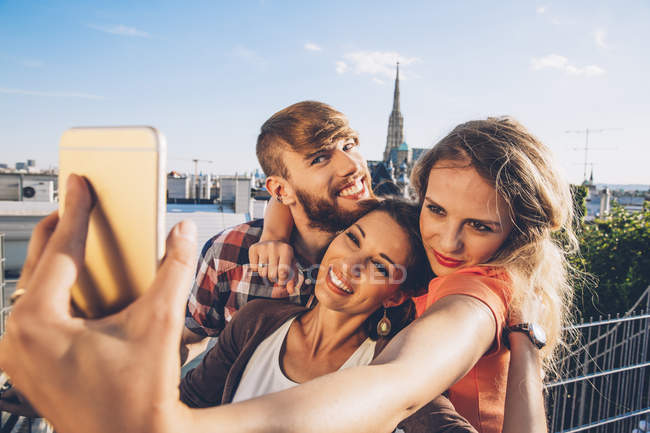 Austria, Vienna, three friends taking selfie on rooftop terrace with Stephansdom in the background — Stock Photo